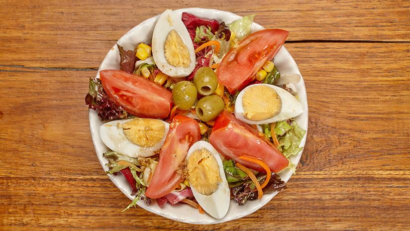 Ensalada mediterránea: Lechuga gourmet, tomate, huevo duro, zanahoria, olivas, maiz y vinagreta de frutos secos.