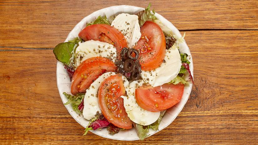Ensalada caprese: Mezclum de lechugas, mozzarella, tomate, albahaca, olivas y salsa tapenade.