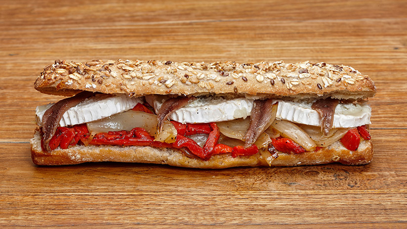 Bocadillo de queso de cabra con parrillada de verduras y anchoas y Pan de semilla.