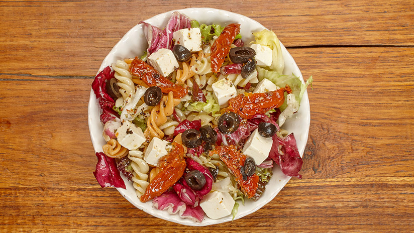 Ensalada de pasta fusilli: Brotes de ensalada, queso feta, olivas negras, tomate deshidratado y aliño de orégano.
