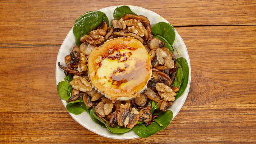 Ensalada de espinacas con: Rulo de cabra, champiñones, nueces y aliño dulce de mostaza.