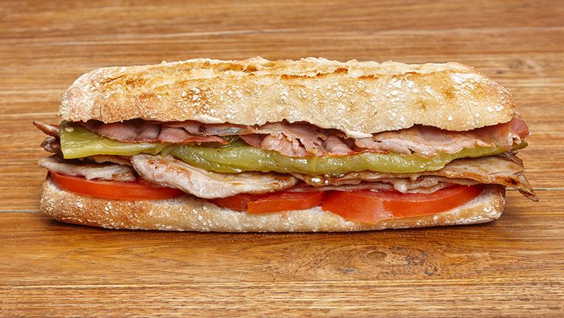 Bocadillo de Solomillo de cerdo en salsa de boletus con jamón serrano, tomate y pimiento verde asado.